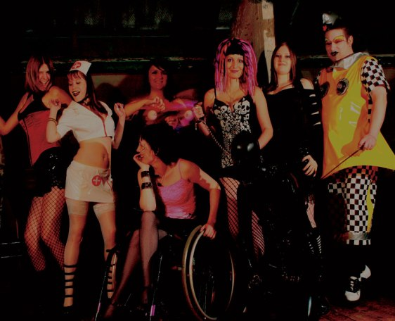 Differnet people all posing together, one in a wheelchair, one gay, others Goth or transgender